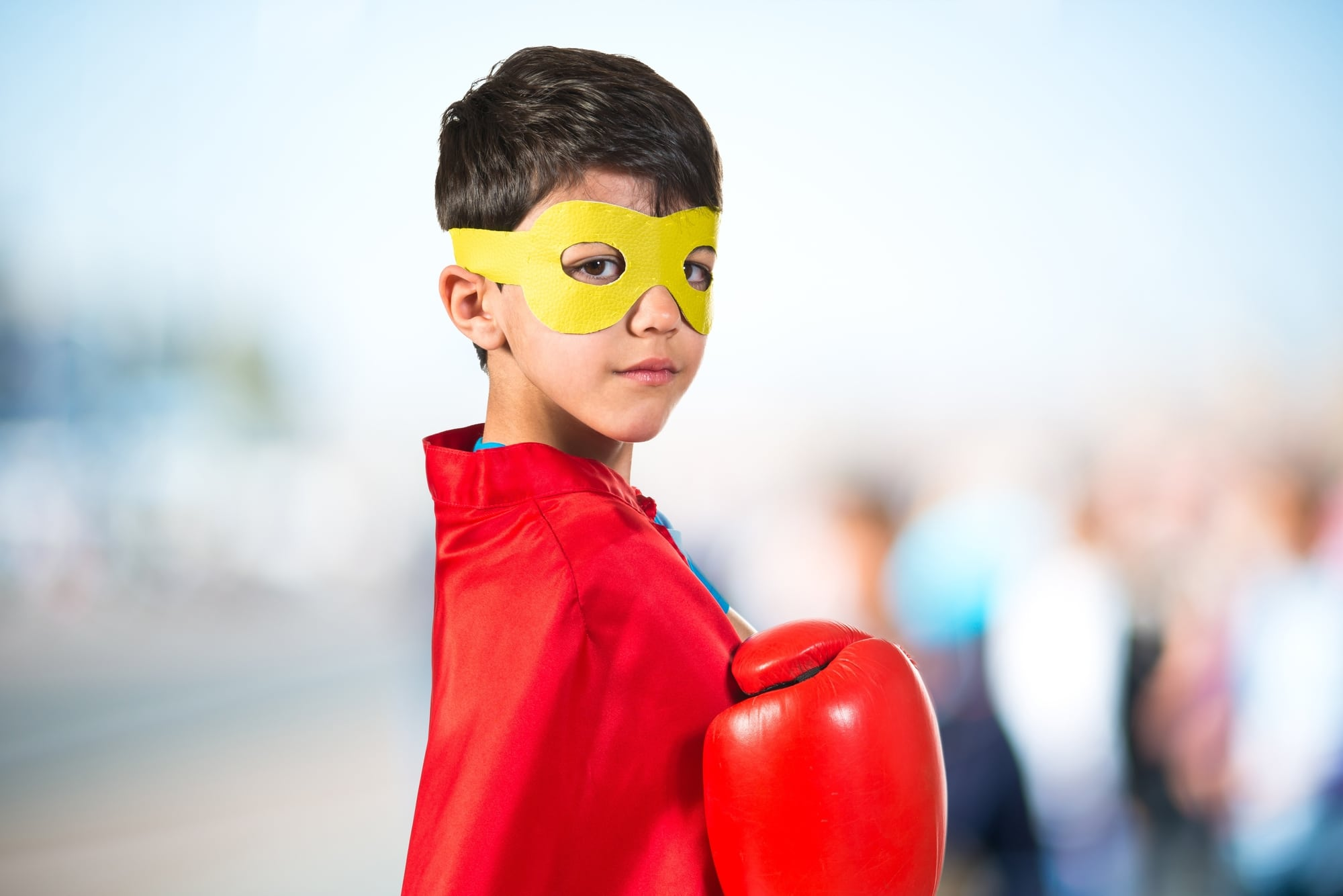 Confident child dressed like superhero with boxing gloves